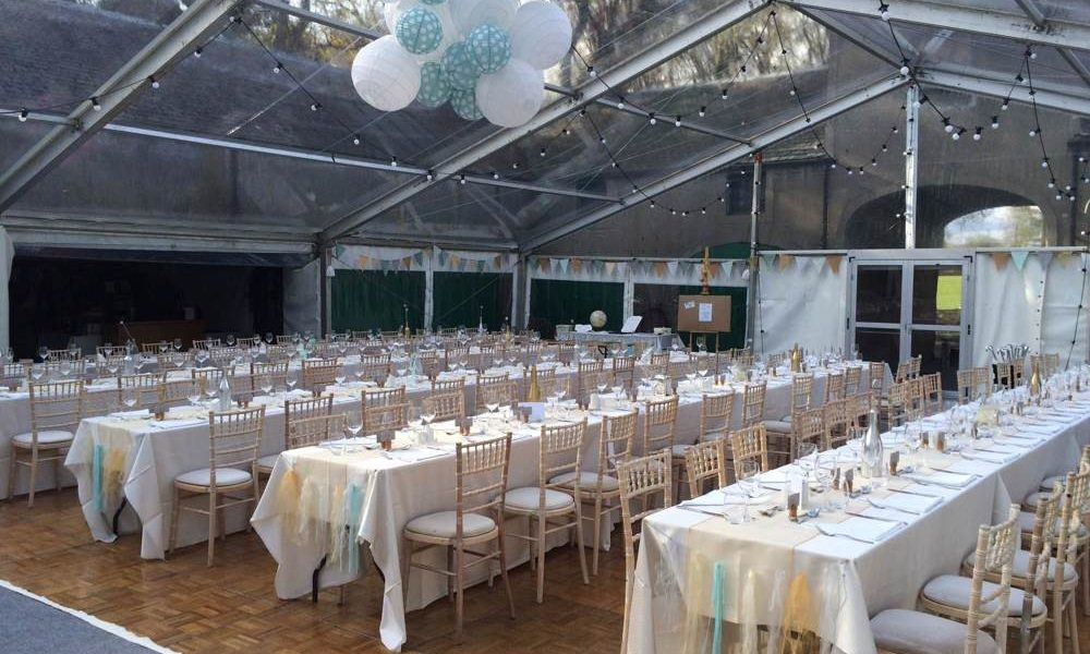 Windows - Trestle tables in courtyard marquee